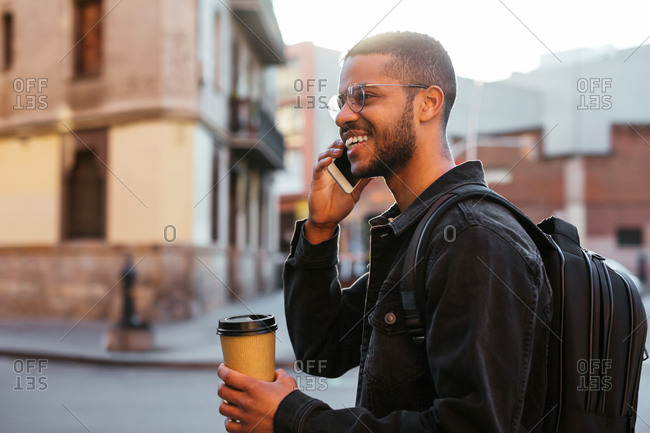 Happy young man talking on the phone, holding a take away coffee while he is standing in the street.