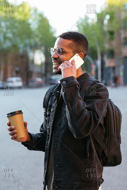Young man talking on the phone, holding a take away coffee while he is standing in the street.