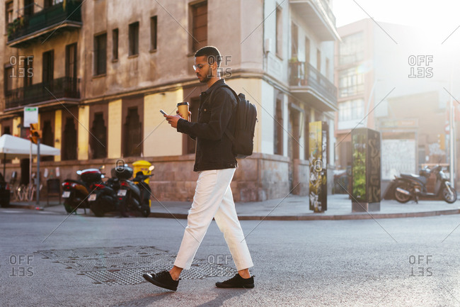 Young man using a mobile phone, holding a take away coffee while he is walking in the street.