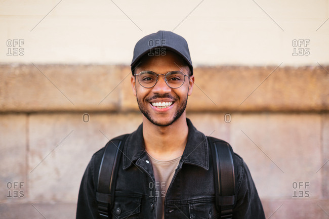 Portrait of a happy young man with a cap smiling in the street