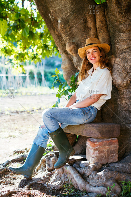 Woman resting in a bench next to a tree in a vegetable garden.