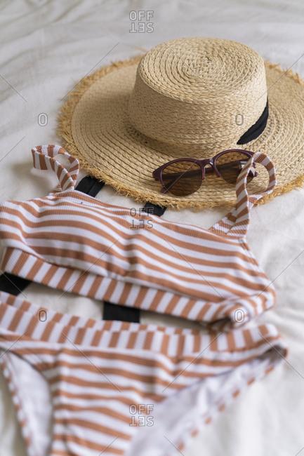 Bikini and straw hat lying on bed