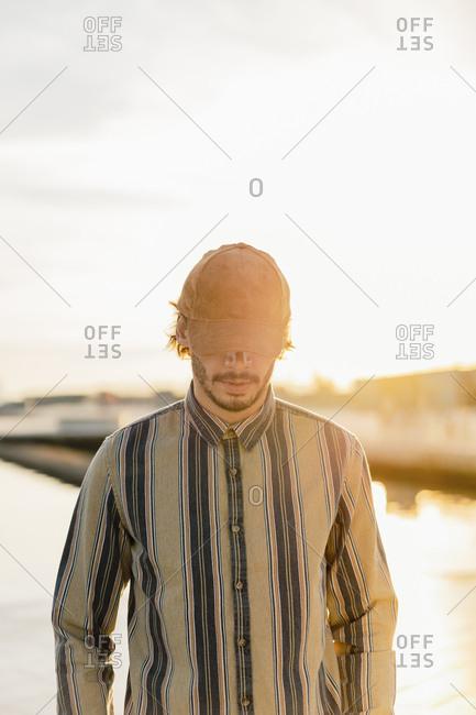 Man wearing baseball cap at sunset