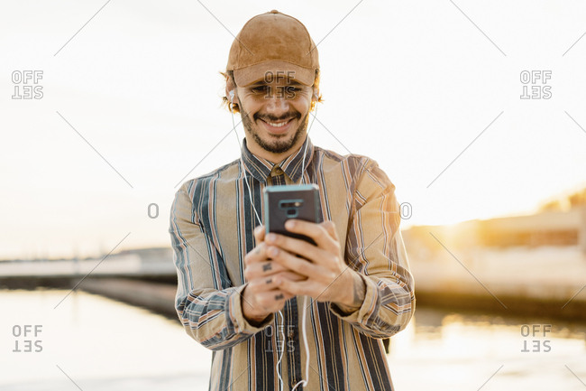 Portrait of smiling man wearing baseball cap listening music with earphones and smartphone at sunset