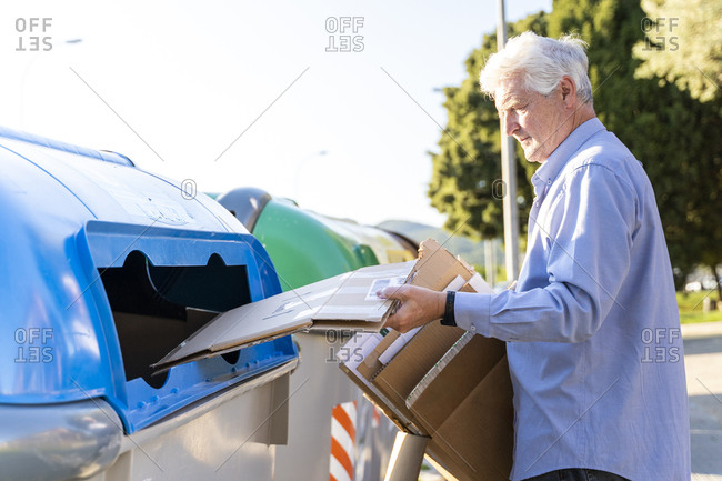 Senior man recycling cardboard in paper bank