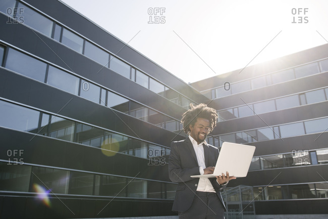 Smiling businessman using laptop outside office