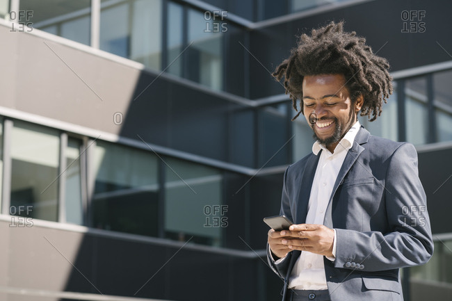 Smiling businessman using cell phone outside office