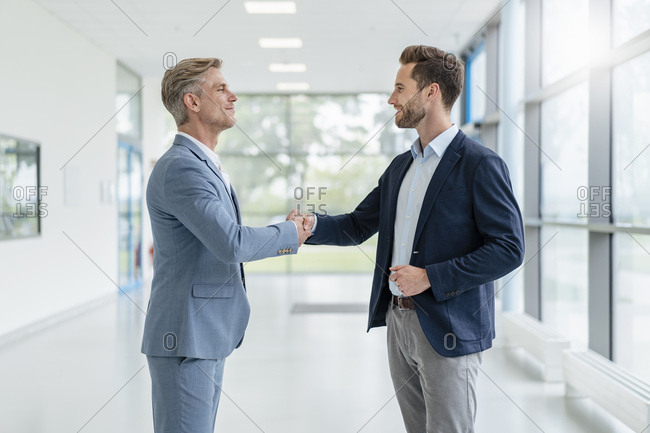 Two businessmen shaking hands in a passageway