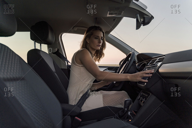 Blond woman driver choosing a radio channel in her car