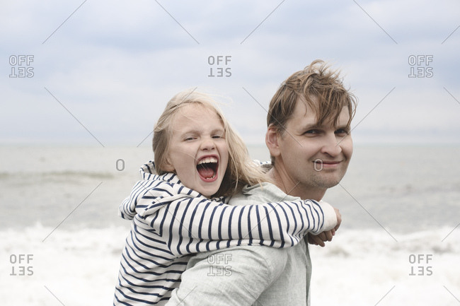 Portrait of smiling father carrying his carefree daughter piggyback at the sea