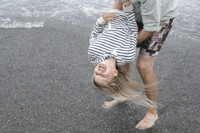Father playing with his daughter on the beach