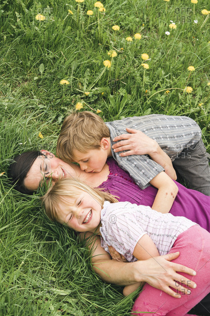 Mother with two children lying on meadow in the countryside