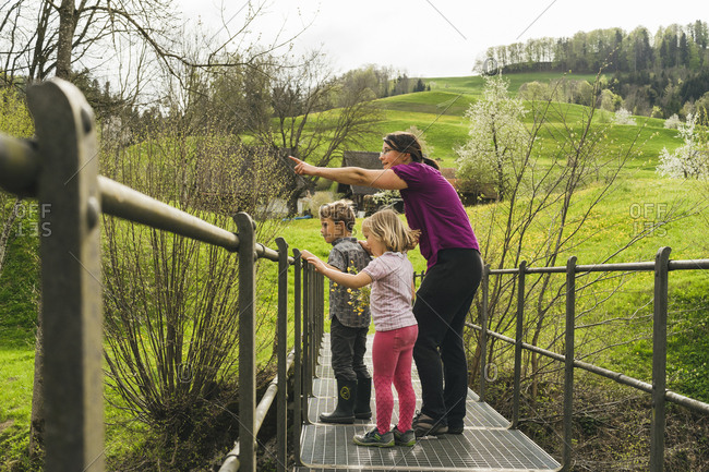 Mother with two children on a bridge in the countryside