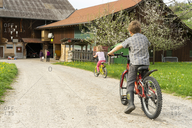 Girl and boy riding bicycle at a farm