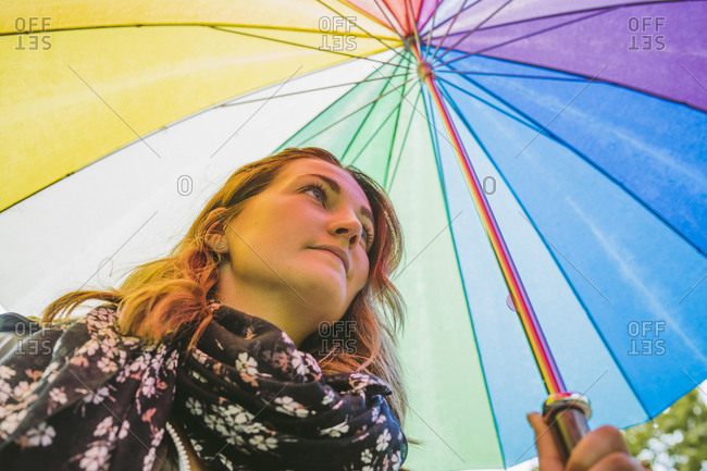 Young woman under colorful umbrella