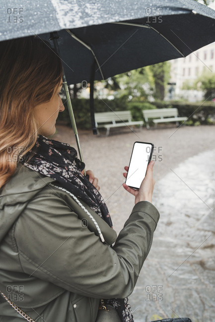 Young woman using cell phone on a rainy day