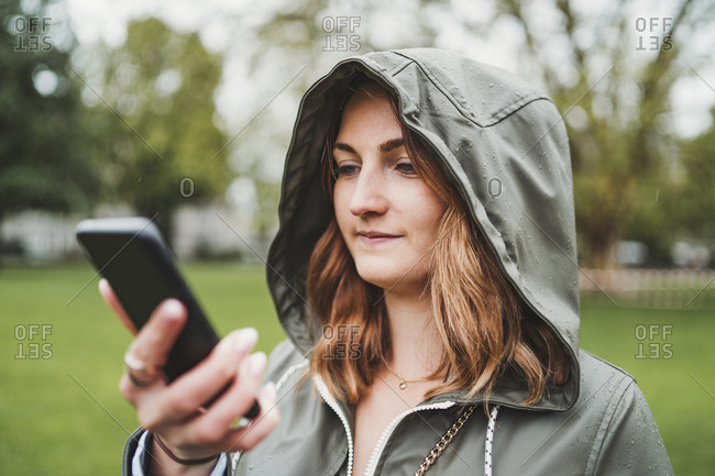 Young woman wearing hooded jacket and using cell phone on a rainy day