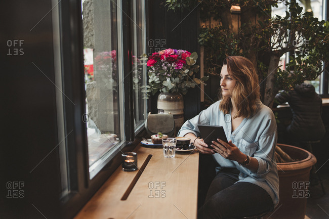 Young woman with an e-book in a cafe