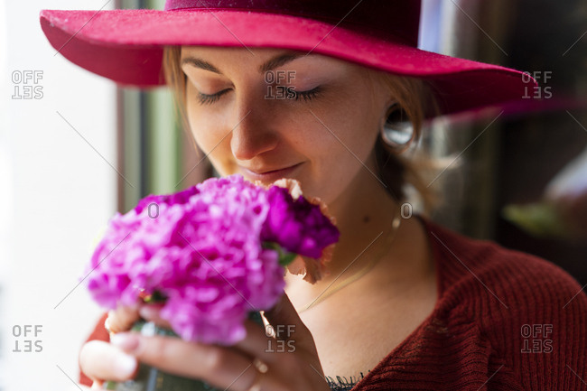 Young woman smelling at flower