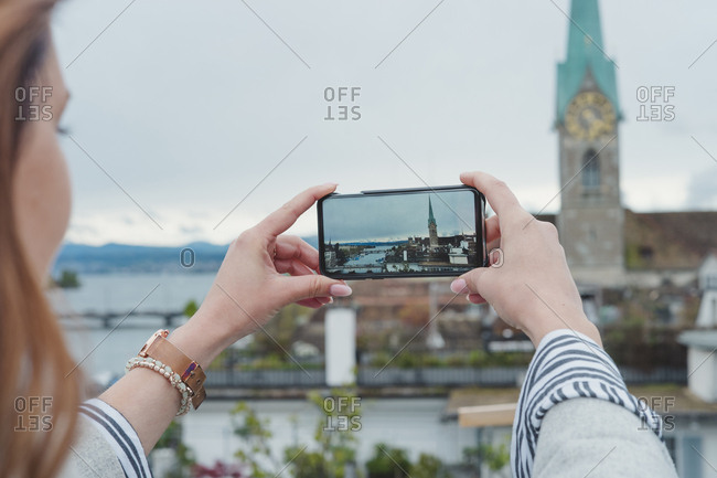 Young woman taking smartphone picture in the city- Zurich- Switzerland