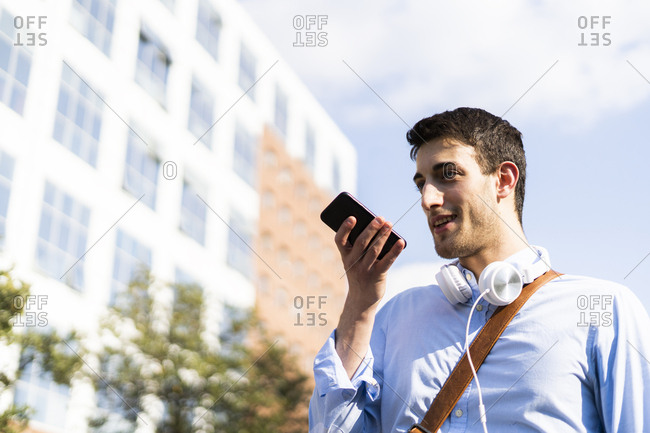 Young man using smartphone- headphones around neck in the city