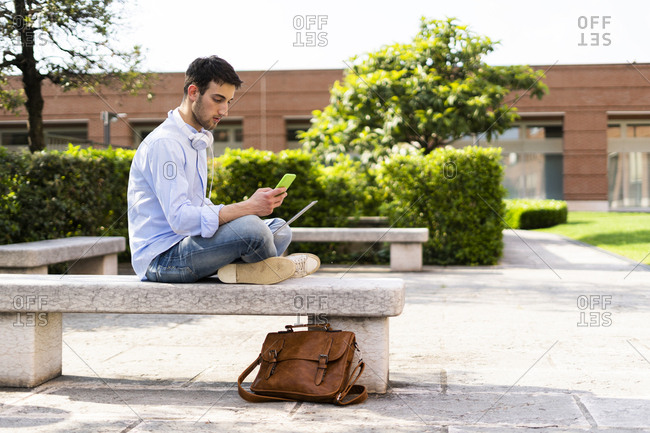 Young man using laptop and smartphone- headphones around neck- sitting on a bench