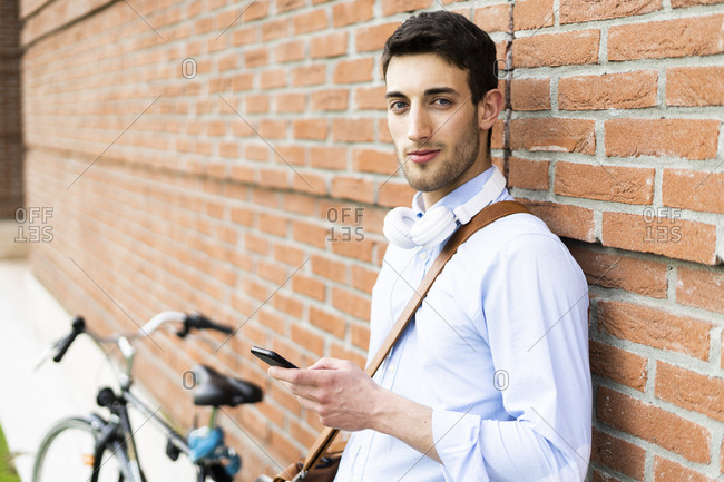 Young man with bicycle using smartphone- headphones around neck