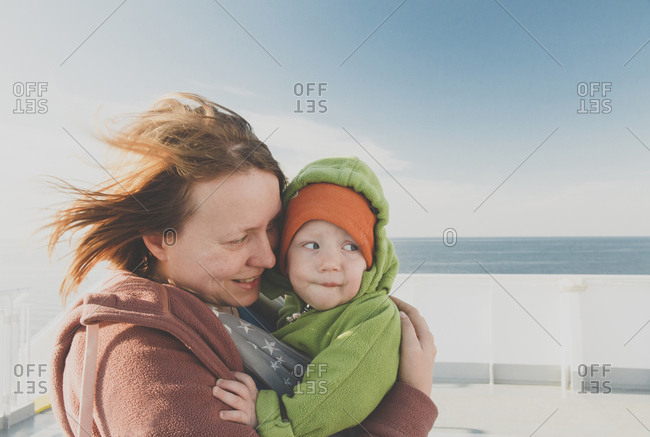 Mother carrying baby boy in a sling on a ferry