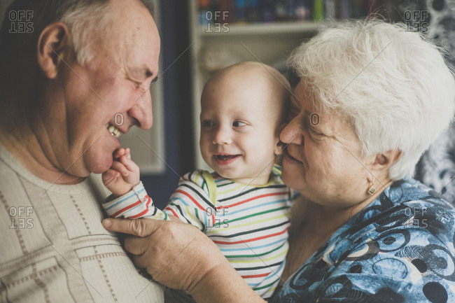 Happy grandparents holding their baby grandson