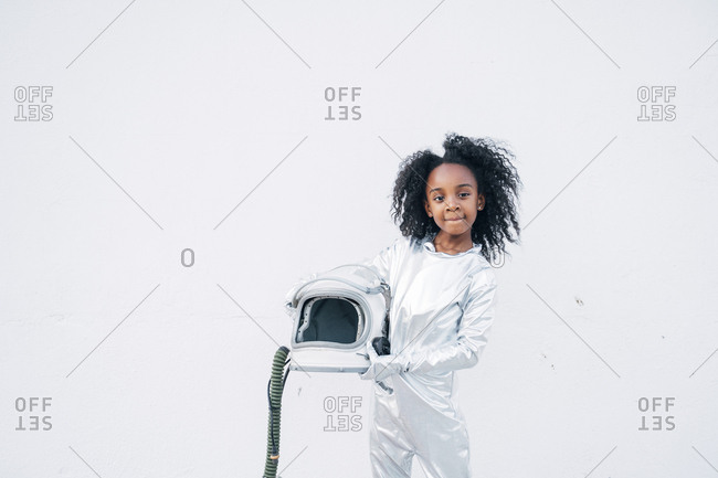 Portrait of little girl wearing space suit in front of white background