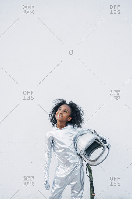 Portrait of smiling little girl wearing space suit in front of white background looking up