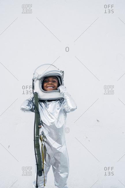 Smiling little girl wearing space suit putting on space hat in front of white background