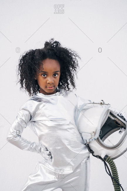 Portrait of little girl with space hat wearing space suit in front of white background