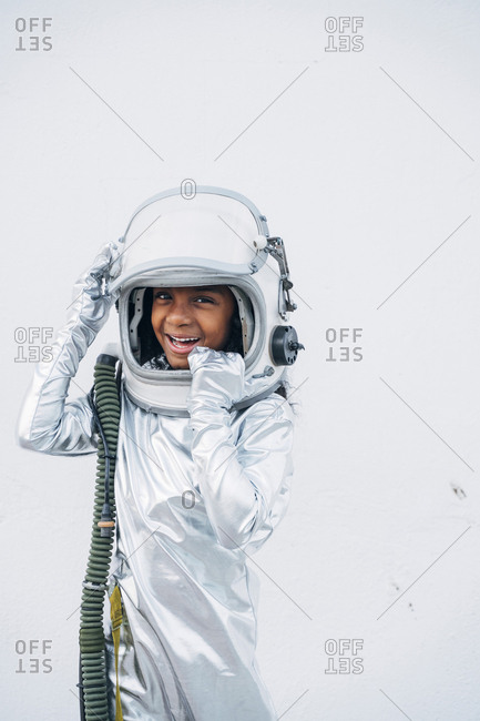 Portrait of laughing little girl wearing space suit and space hat in front of white background