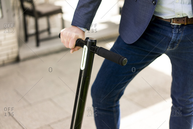 Businessman with E-Scooter- partial view