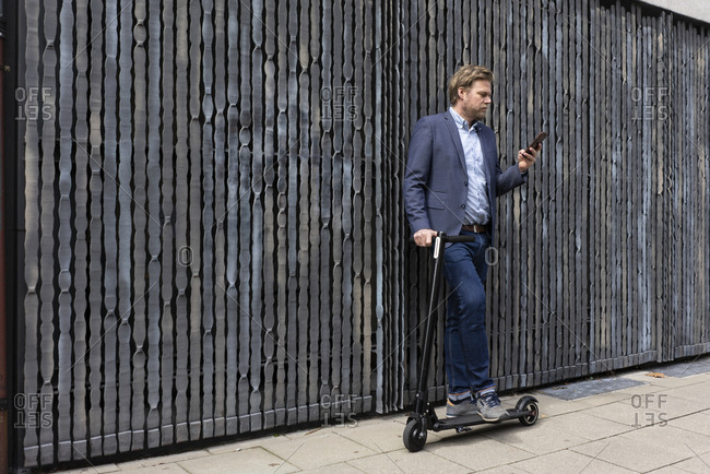 Businessman standing on pavement with  E-Scooter looking at cell phone