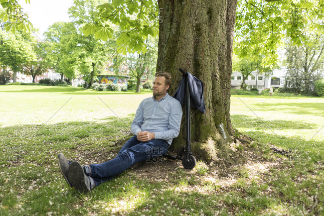 Businessman sitting on E-Scooter in a park leaning against tree trunk relaxing