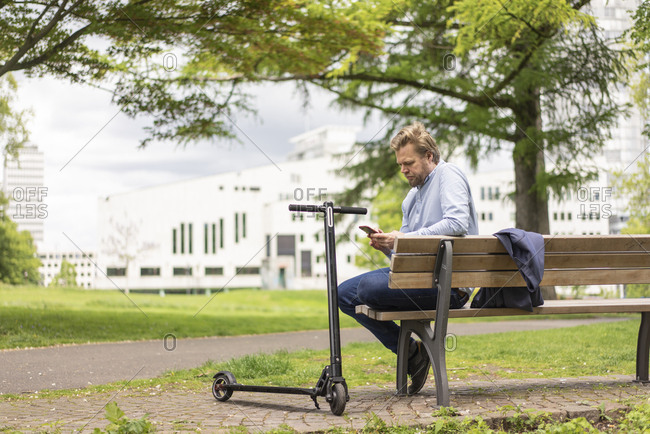 Businessman with E-Scooter sitting on bench in city park using smartphone- Essen- Germany