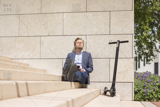 Businessman with E-Scooter and smartphone sitting on steps relaxing