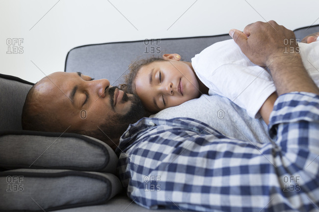Father and daughter sleeping on couch at home
