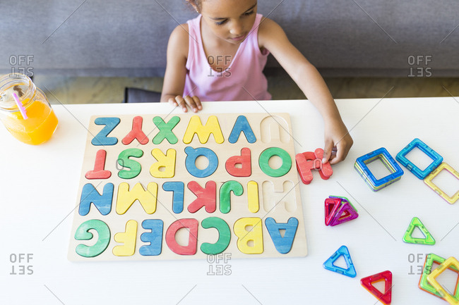 Girl playing with alphabet learning game at home