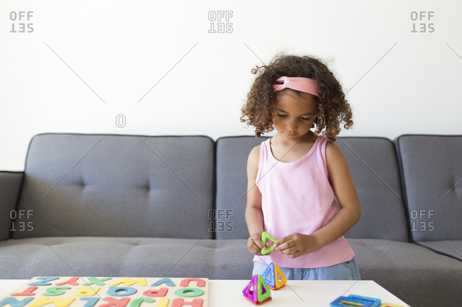 Girl playing with learning game at home