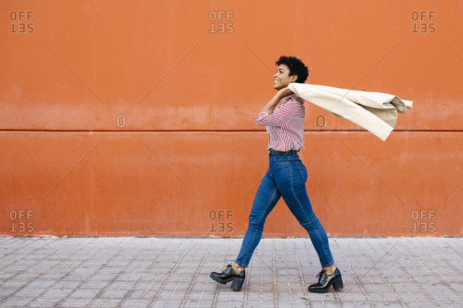 Businesswoman walking at a red wall in the background- putting her jacket on her shoulder