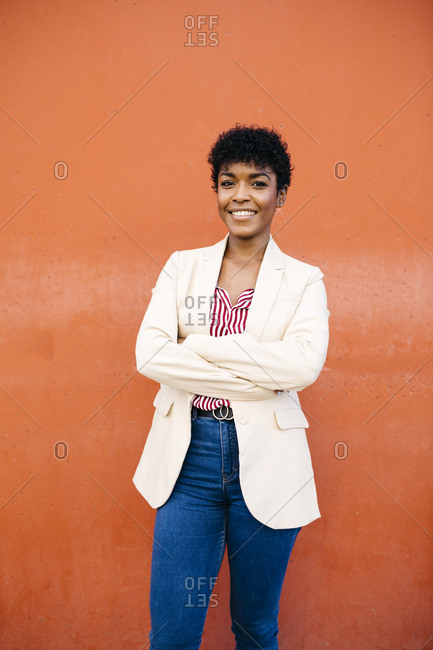 Portrait of smiling businesswoman with a red wall in the background