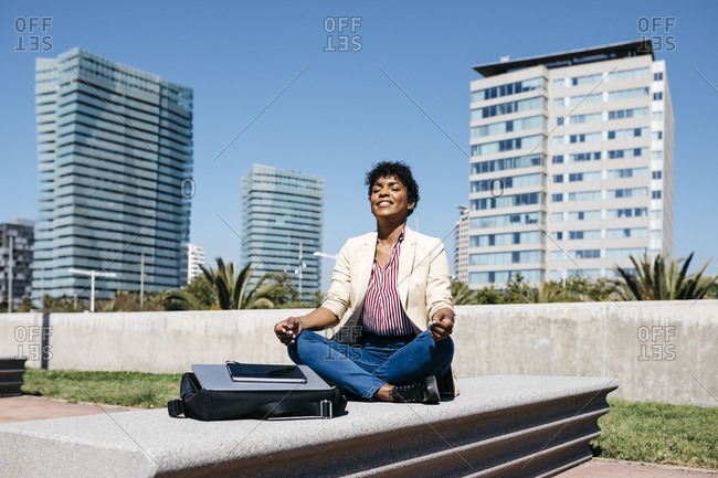 Businesswoman sitting on bench and meditating