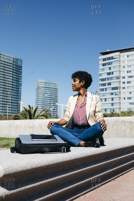 Businesswoman sitting on bench and- laptop and tablet on bag