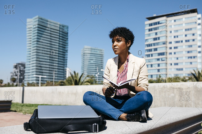 Businesswoman sitting on bench with notebook- laptop on bag