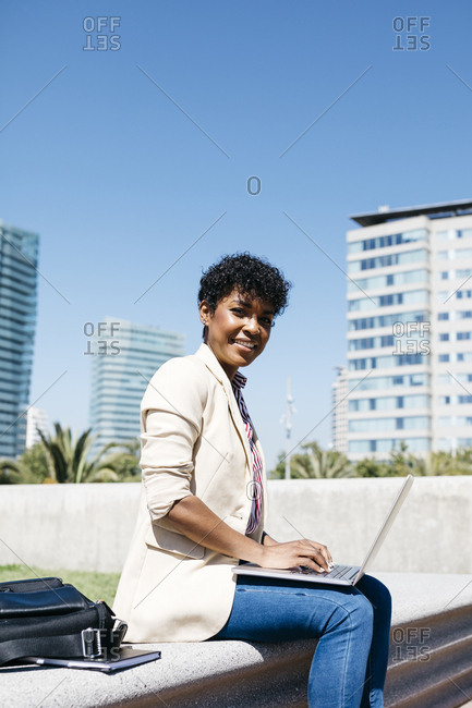 Businesswoman working with laptop- sitting on a bench on a sunny day