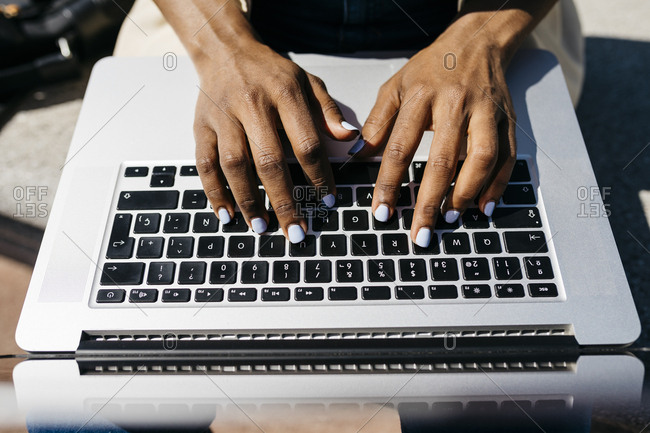 Businesswoman sitting on bench and using laptop finger typing