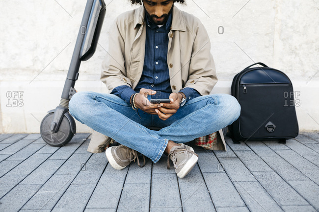 Man sitting on his E-Scooter using mobile phone
